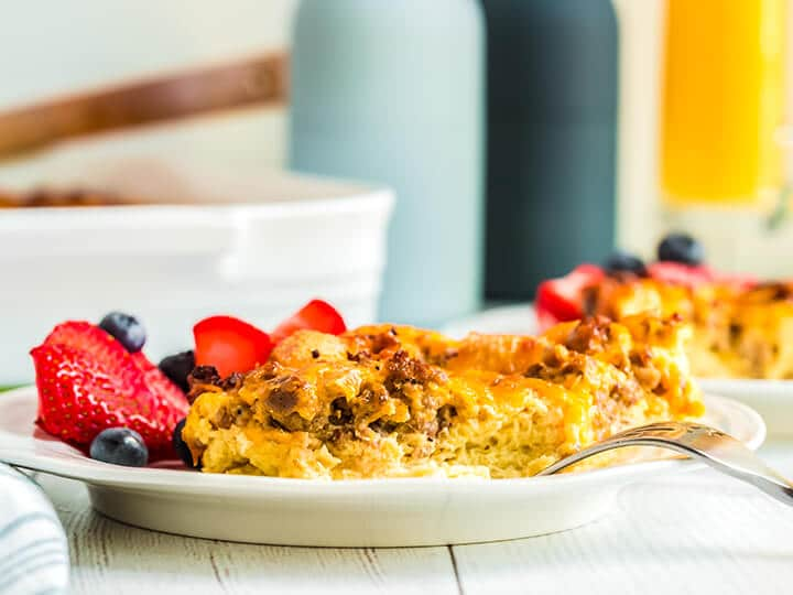A serving of overnight breakfast casserole on a white plate with a fork.