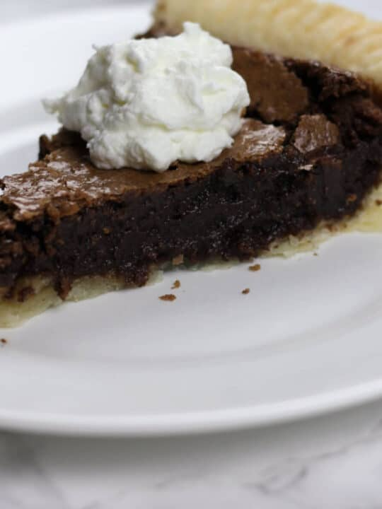 A slice of fudge pie on a white plate.