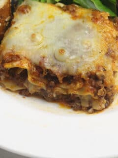 A closeup serving of lasagna without ricotta on a white plate.