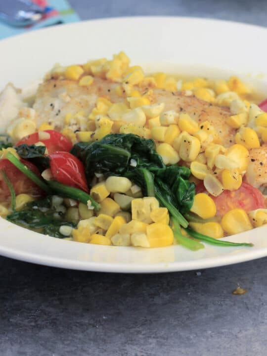 Oven baked fish in a white bowl with fresh summer vegetables like spinach, corn, and tomatoes will be one of your weeknight favorites! This recipe is quick and easy and everyone loves it!