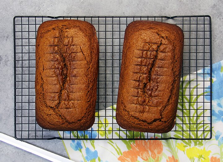 Two loaves of pumpkin bread on a rack.