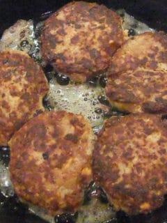 Salmon patties in a skillet frying.