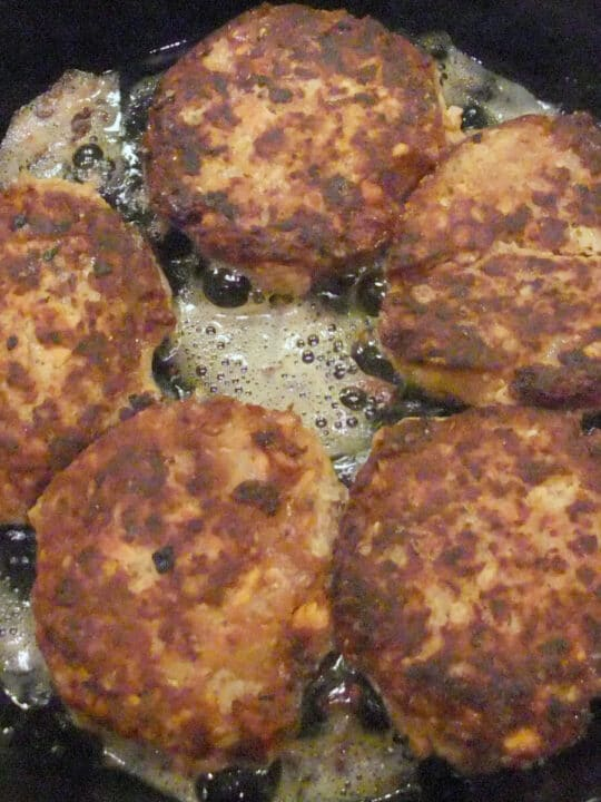 Salmon patties in a skillet frying.