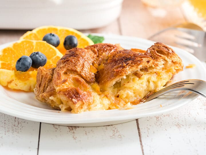 A serving of croissant breakfast casserole on a white plate with orange slices and blueberries in the background.