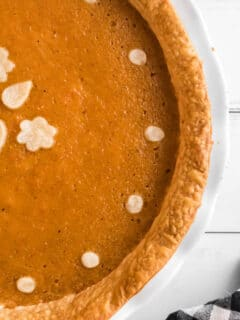 Overhead view of half a sweet potato pie in a white plate.