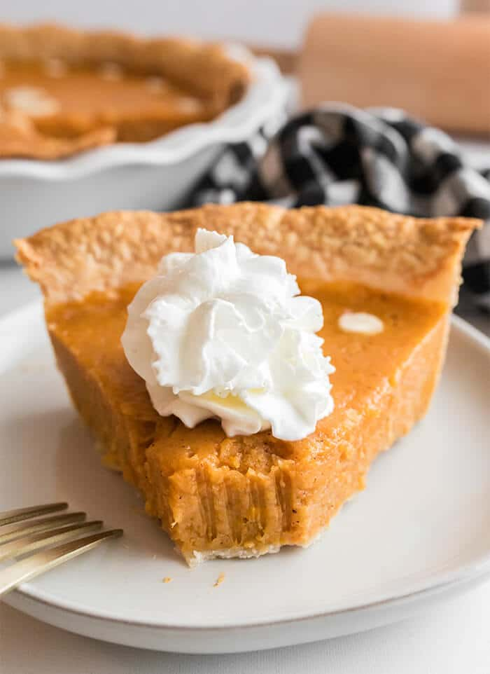 A slice of Southern sweet potato pie with a bite taken out and a fork on the white plate.