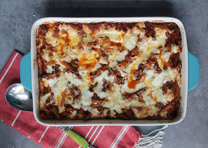 A blue baking dish filled with pasta bake with chicken on a red striped towel with a spoon.