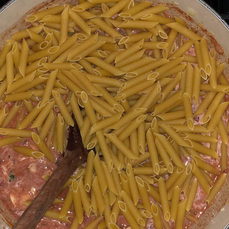 A wooden spoon stirring penne pasta into a pot of sauce.