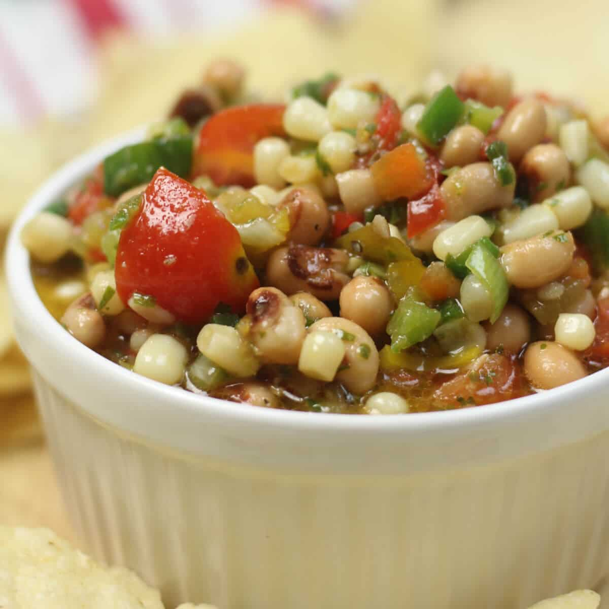 A white bowl filled with texas caviar and surrounded by chips.