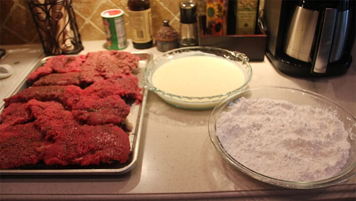 A pan filled with cube steak beside a dish of buttermilk and a dish of flour.