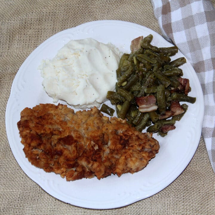 Overhead photo of a white plate with a piece of cube steak, green beans, and mashed potatoes.