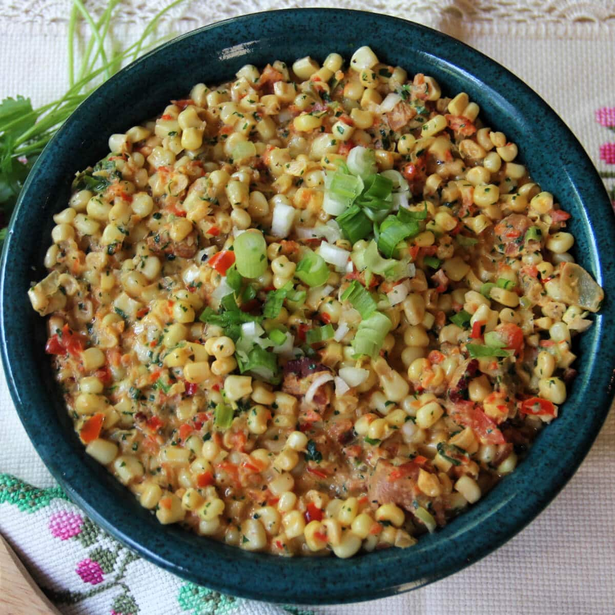Jalapeno creamed corn with bacon, scallions, and cilantro is a great side dish for taco night, burgers on the grill, or slow-roasted pork. This cream style corn is a little spicy and everyone loves it!