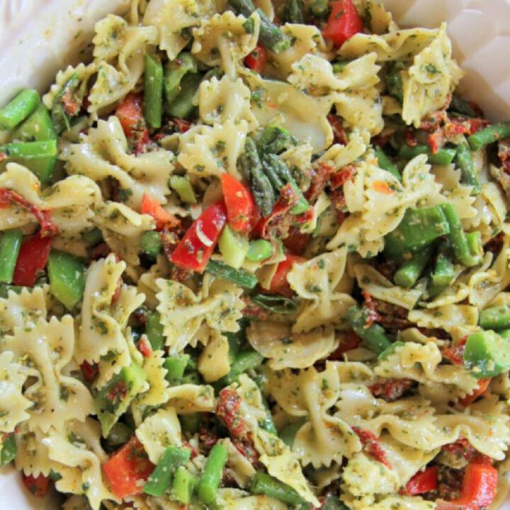 A bowl of pesto pasta salad with lemon basil pesto salad dressing, along with bowtie pasta, sundried tomatoes, asparagus, artichoke hearts, and more lemon zest.