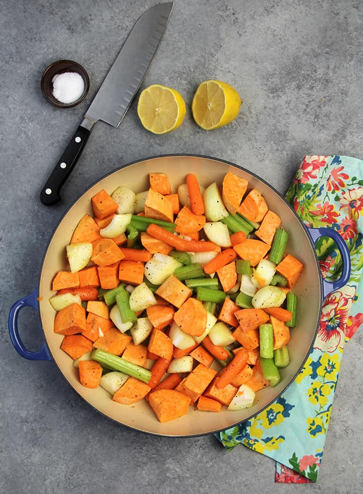 Chopped vegetables in a blue braiser with a knife on the side.