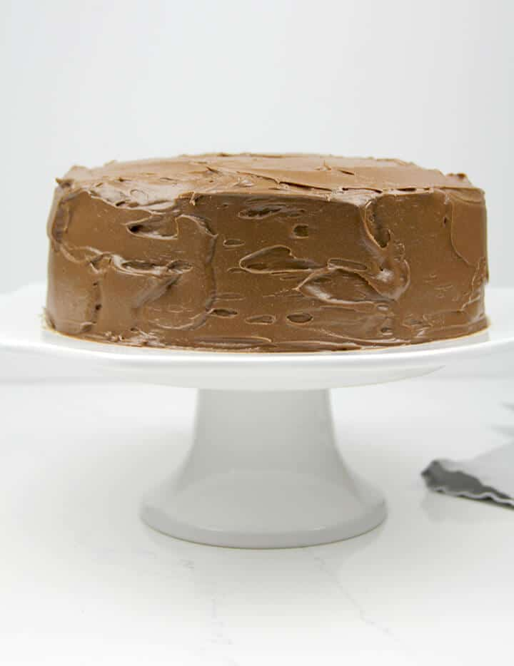 Chocolate frosted cake on a white cake stand.