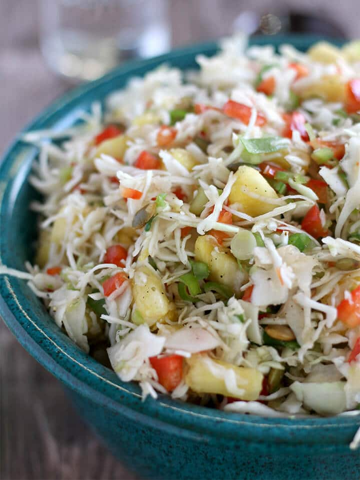 A blue bowl filled with pineapple coleslaw.