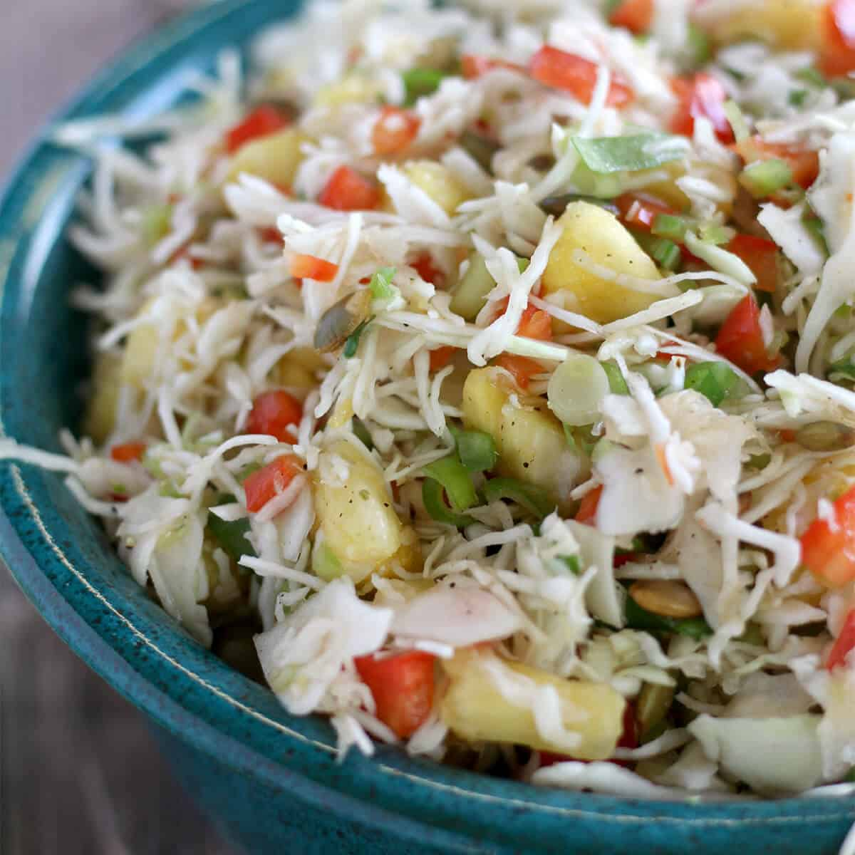 Closeup photo of pineapple slaw in a blue pottery bowl.